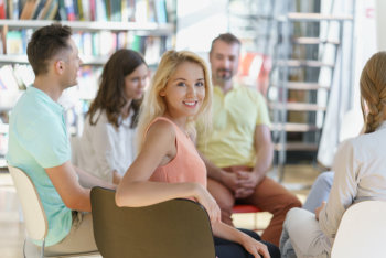 woman smiling while attending group therapy